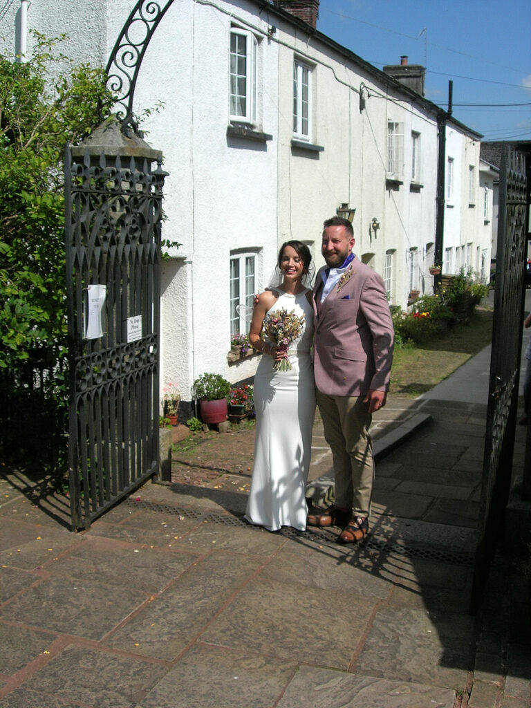 Bride and groom standing by the church gates