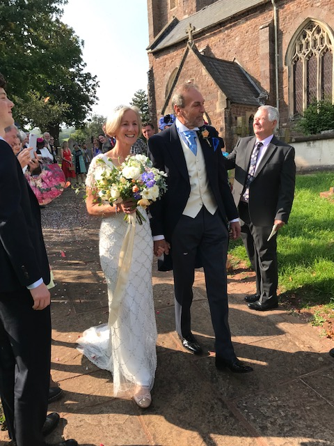 Bride and groom walking down the church path as guests throw confetti